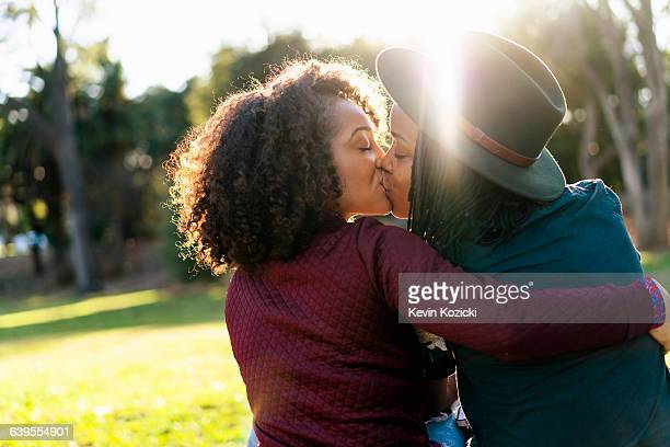 lesbian couple kissing in the park - lesbica bacio foto e immagini stock