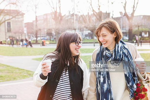 lesbian couple laughing walking in urban square.