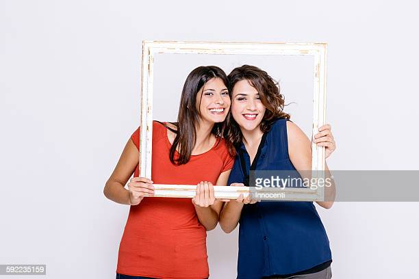 lesbian couple looking through picture frame at camera smiling - looking through an object stock pictures, royalty-free photos & images