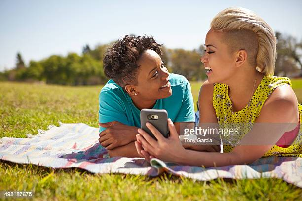 lesbian couple lying on picnic blanket in park - half shaved hairstyle stock pictures, royalty-free photos & images