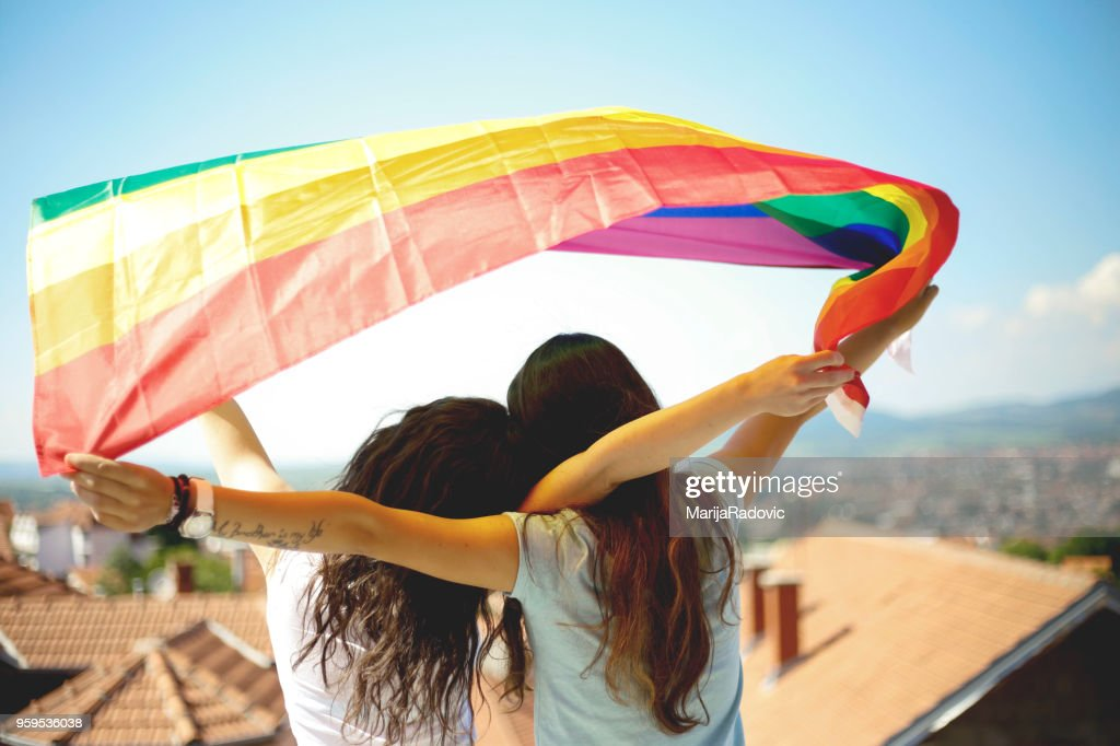 LGBT-lesbisches paar Momente Glück Konzept. Regenbogenfahne halten im freien : Stock-Foto