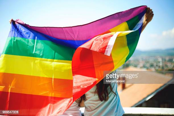 LGBT Lesbian couple moments happiness concept. Holding rainbow flag outdoors