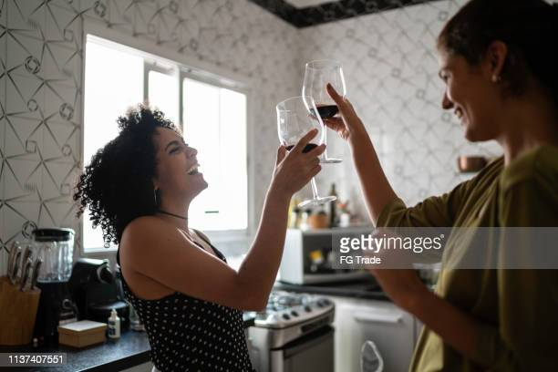 lesbian couple on celebratory toast at kitchen - brindisi bicchieri foto e immagini stock