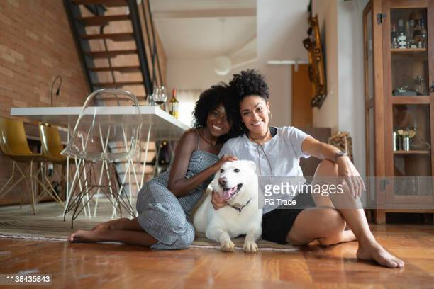 casal de lésbicas ou amigos com berger blanc suisse dog em casa - um animal - fotografias e filmes do acervo