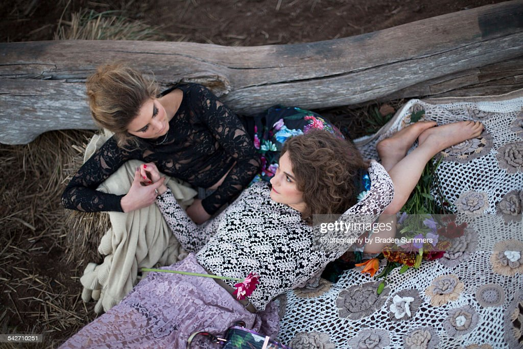 Lesbian couple outdoors on blanket. : Stock Photo