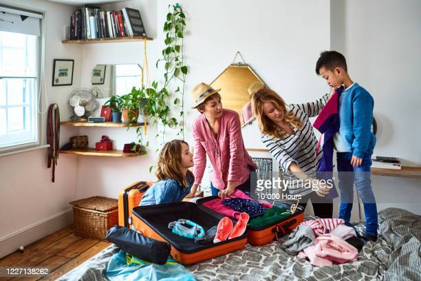 lesbian couple packing suitcases for holiday with children - vacations stock pictures, royalty-free photos & images