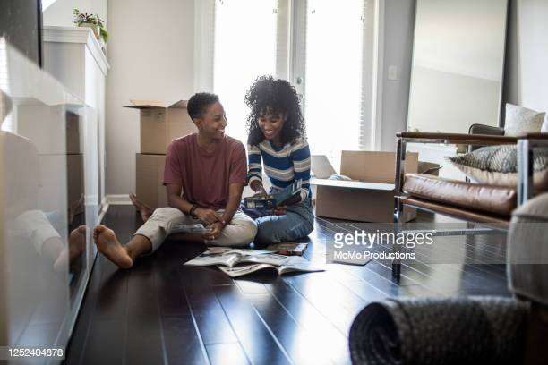 lesbian couple picking paint colors for new home - lgbtq  and female domestic life stock pictures, royalty-free photos & images
