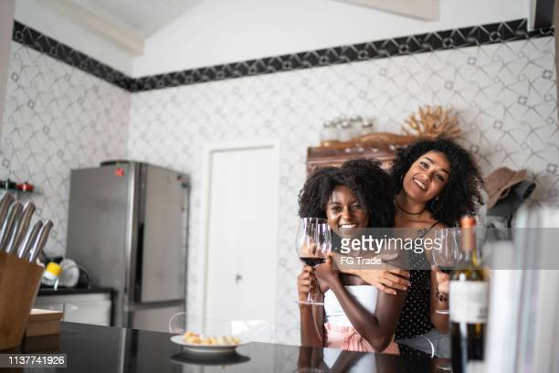 lesbian couple portrait drinking wine at kitchen - lesbian date stock pictures, royalty-free photos & images