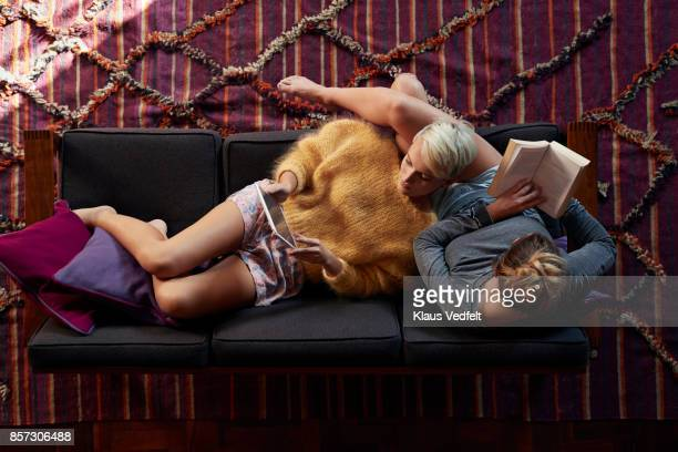 Lesbian couple relaxing and reading in couch