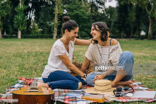 lesbian couple relaxing outdoors in a park - lesbian dating stock pictures, royalty-free photos & images
