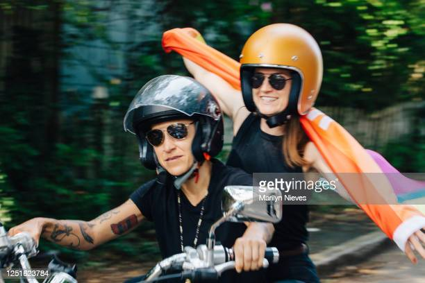 """lesbian couple riding around town with pride flag - """"marilyn nieves"""" stock pictures, royalty-free photos & images"""