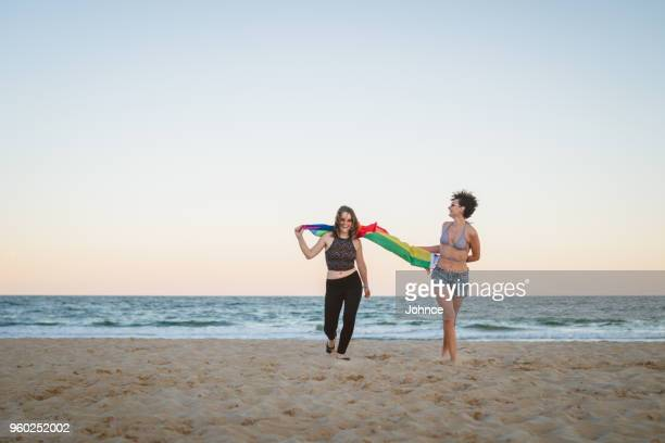 Lesbian couple running with rainbow flag