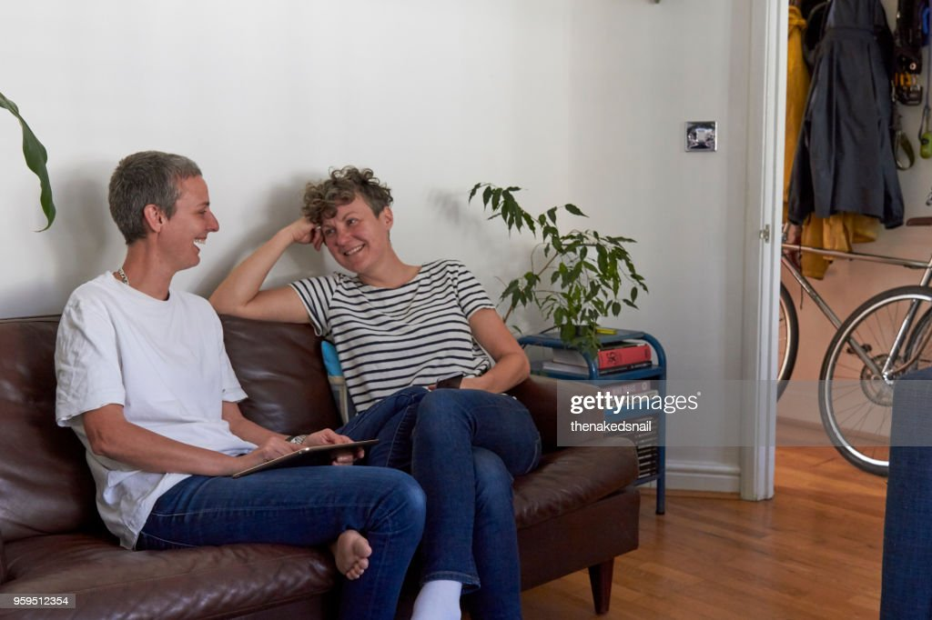 Lesbian couple sitting on sofa with tablet : Stock-Foto