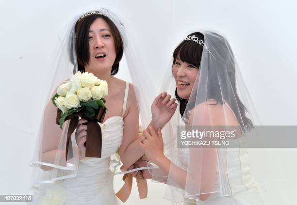 A lesbian couple smiles as they pose for photos taken by a wedding photo service company in Tokyo before participating in the 'Tokyo Rainbow Pride'...