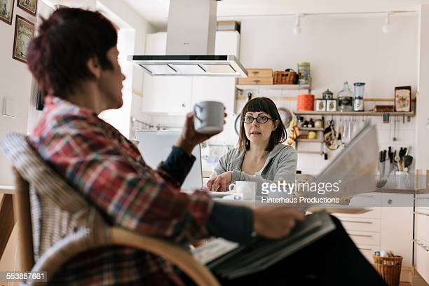 lesbian couple spending time in their kitchen - lgbtq  and female domestic life stock pictures, royalty-free photos & images