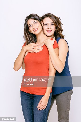 Lesbian Couple Standing Hugging Looking At Camera Smiling Photo - Getty Images-6165