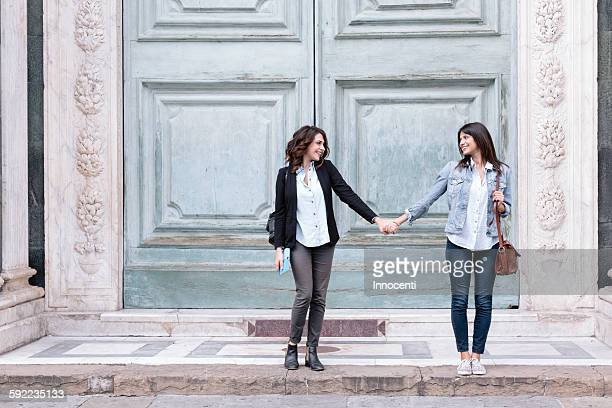 Lesbian couple standing in oversized church doorway holding hands, Piazza Santa Maria Novella, Florence, Tuscany, Italy