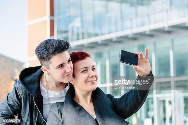 Lesbian couple taking selfie in modern station
