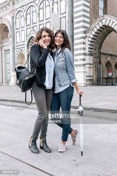 Lesbian couple talking on cellular phone holding umbrella looking at camera smiling, Piazza Santa Maria Novella, Florence, Tuscany, Italy