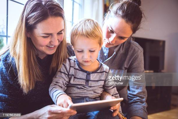 lesbian couple teaching their son how to read using a digital tablet - artificial insemination stock pictures, royalty-free photos & images