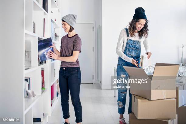 Lesbian couple unpacking cardboard box in new home