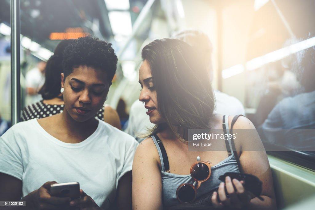 Casal de lésbicas usando o celular no metrô : Foto de stock