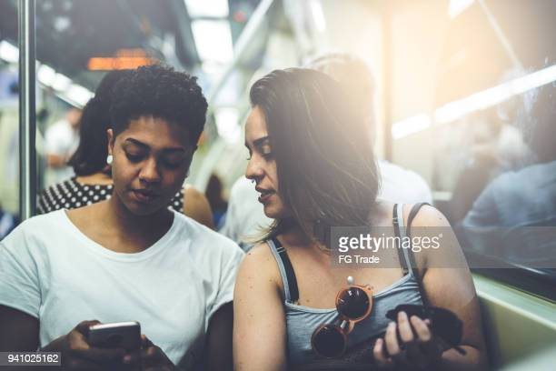 Lesbian Couple Using Mobile at Subway