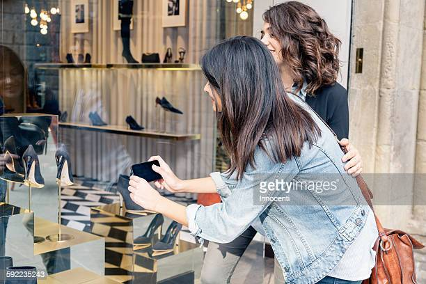 Lesbian couple using smartphone to take photograph of shoes through shoe shop window, Florence, Tuscany, Italy
