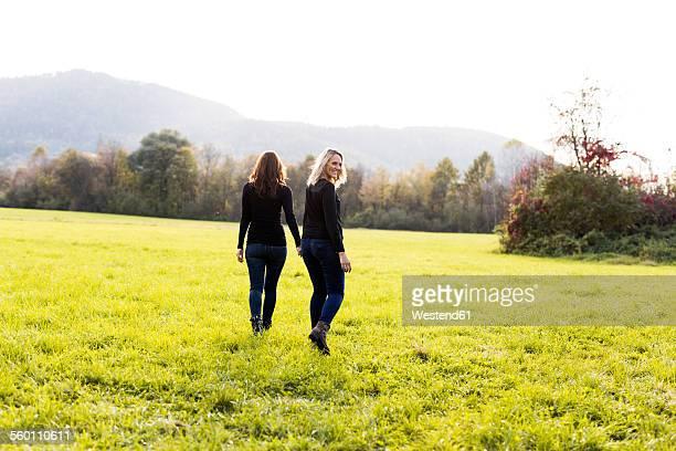 Lesbian couple walking hand in hand on a meadow