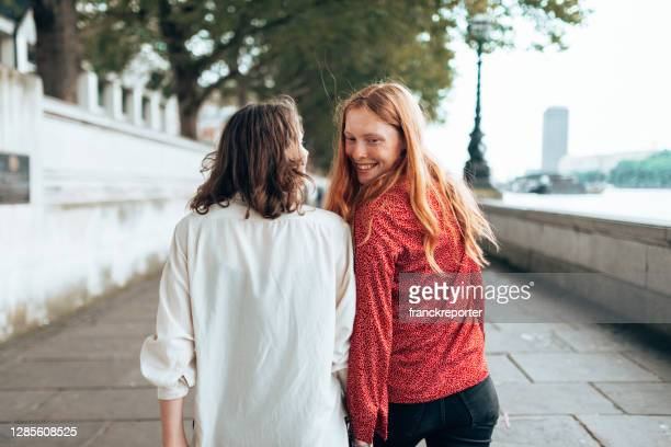 lesbian couple walking happy together on the street - street stock pictures, royalty-free photos & images