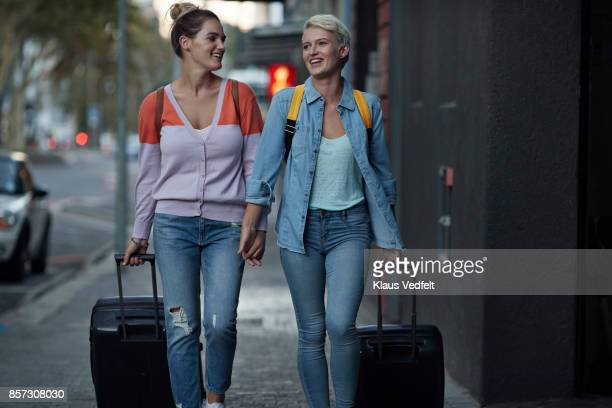 lesbian couple walking together with rolling suitcases - 前をはだけた ストックフォトと画像