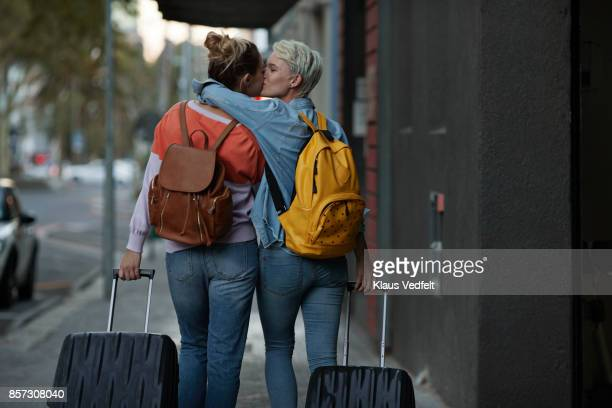 lesbian couple walking together with rolling suitcases - baisers lesbiennes photos et images de collection