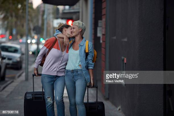 lesbian couple walking together with rolling suitcases - lesbica bacio foto e immagini stock