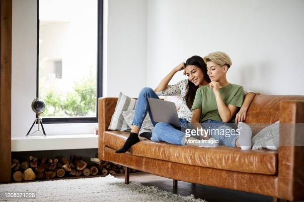 lesbian couple watching movie on laptop at home - gay couple stock pictures, royalty-free photos & images