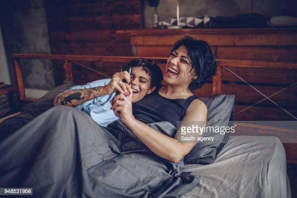 couple de lesbiennes devant la télé - couple au lit photos et images de collection