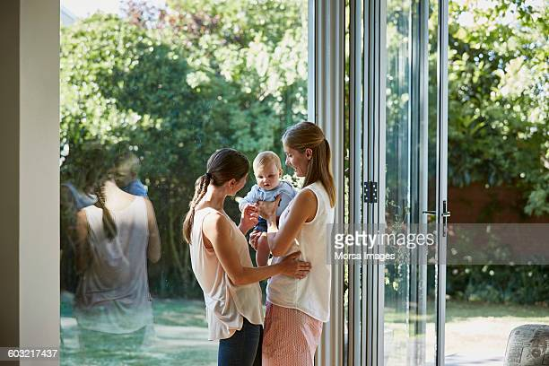 Lesbian couple with baby boy standing by window