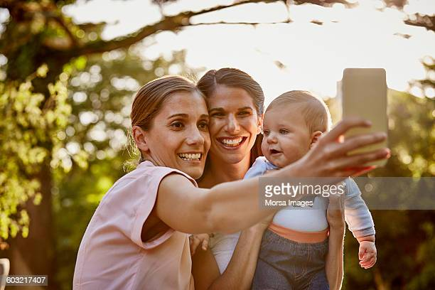 Lesbian couple with baby taking selfie in park