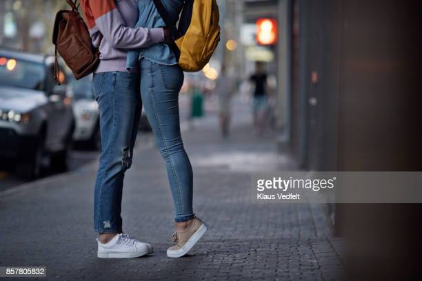 Lesbian couple, with backpacks, hugging on the street