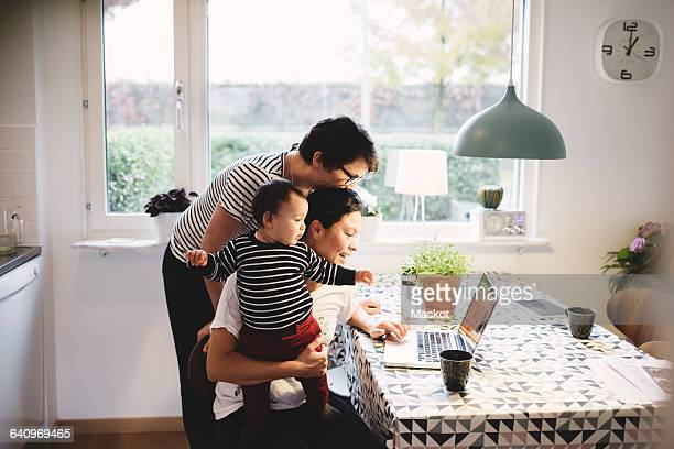 lesbian couple with daughter looking in laptop at kitchen - twee ouders stockfoto's en -beelden