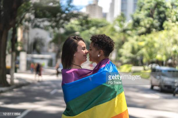 lesbian couple with rainbow flag - lesbica bacio foto e immagini stock