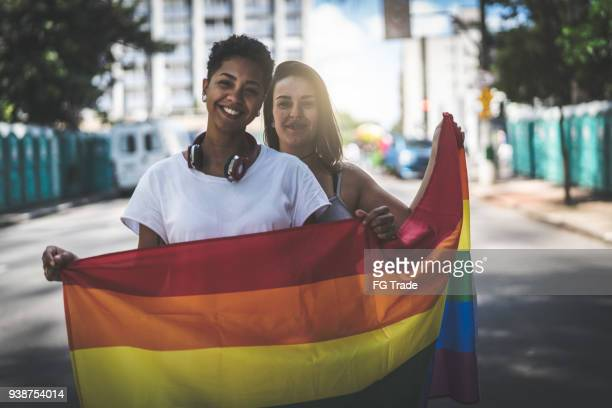 lesbian couple with rainbow flag - pride stock pictures, royalty-free photos & images