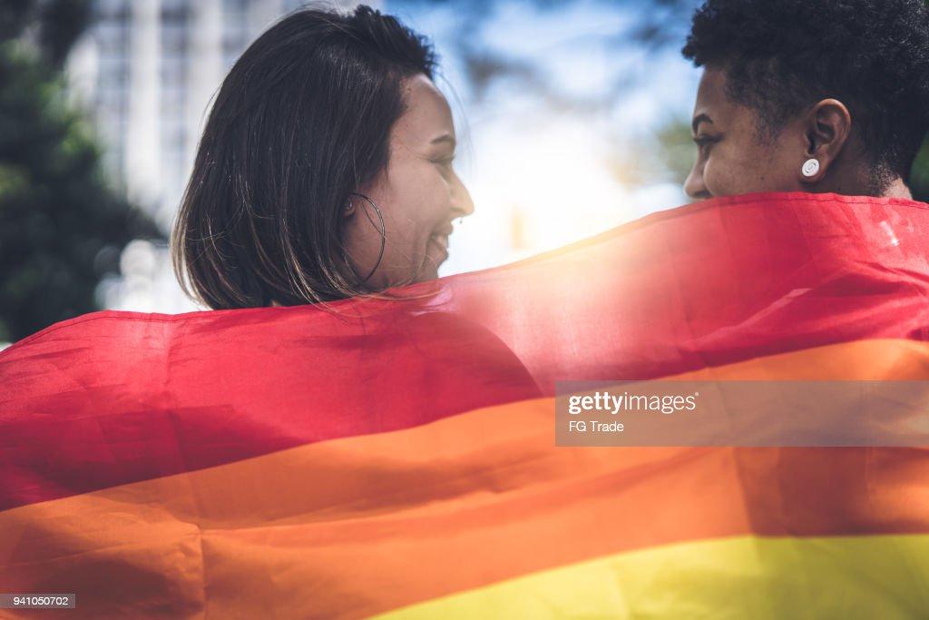 虹色の旗を持つレズビアンのカップル : ストックフォト