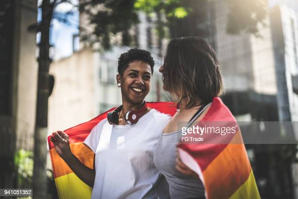 lesbian couple with rainbow flag - campaigner stock pictures, royalty-free photos & images