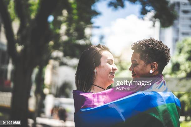 lesbian couple with rainbow flag - prejudice stock photos and pictures