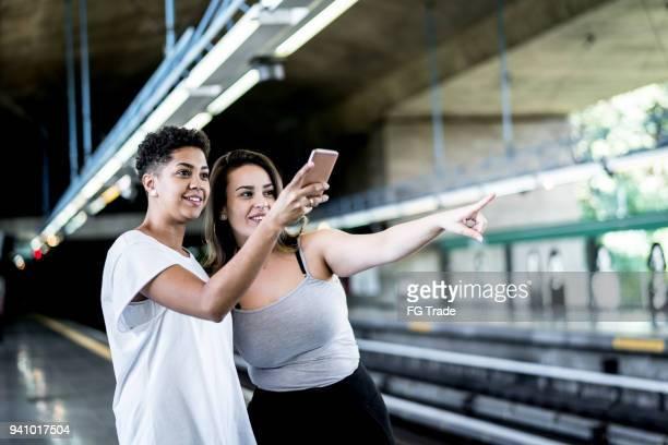 Lesbian Couple/Friends at subway station using smart phone