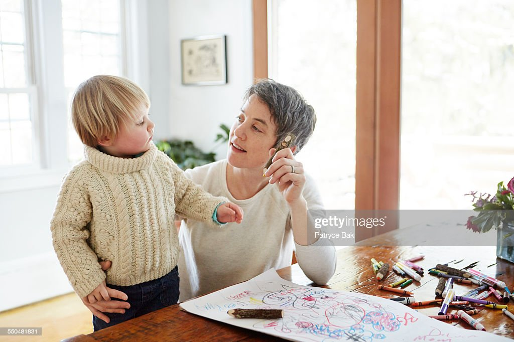 Lesbian mom draws w/ her daughter in dining room : Stock Photo