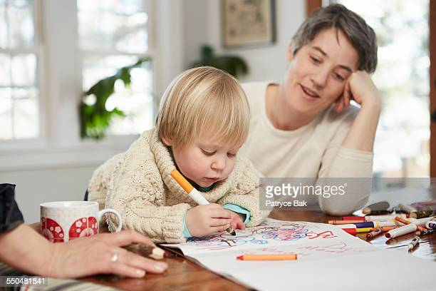 Lesbian moms draw w/ their daughter in dining room