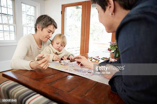Lesbian moms draw with their daughter at home