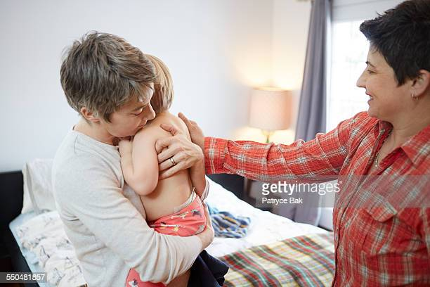 Lesbian moms hug their daughter in the bedroom