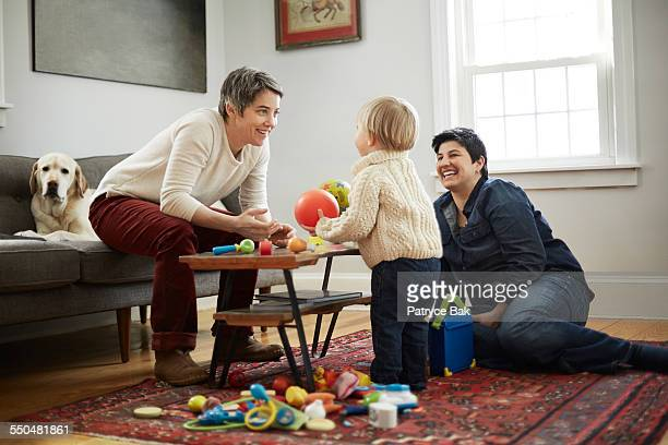 lesbian moms play w/ their daughter in living room - lgbtq  and female domestic life fotografías e imágenes de stock